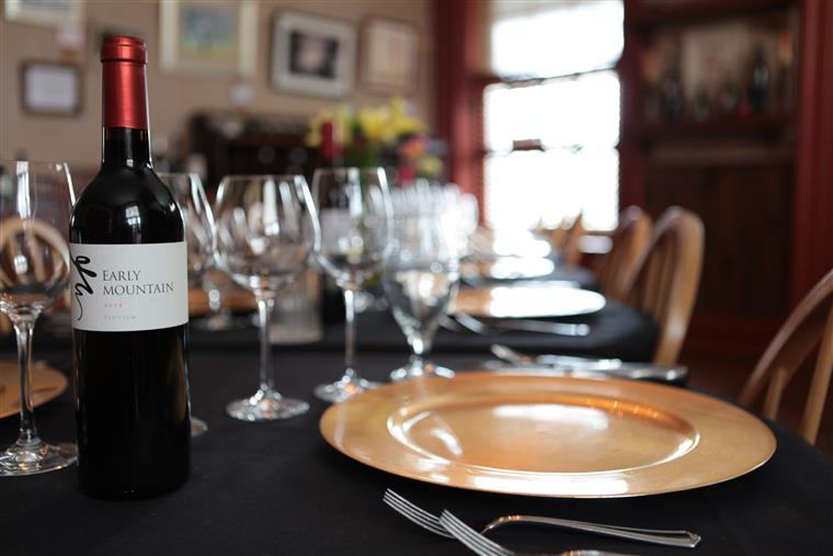 Dining Room setting with bottle of red wine