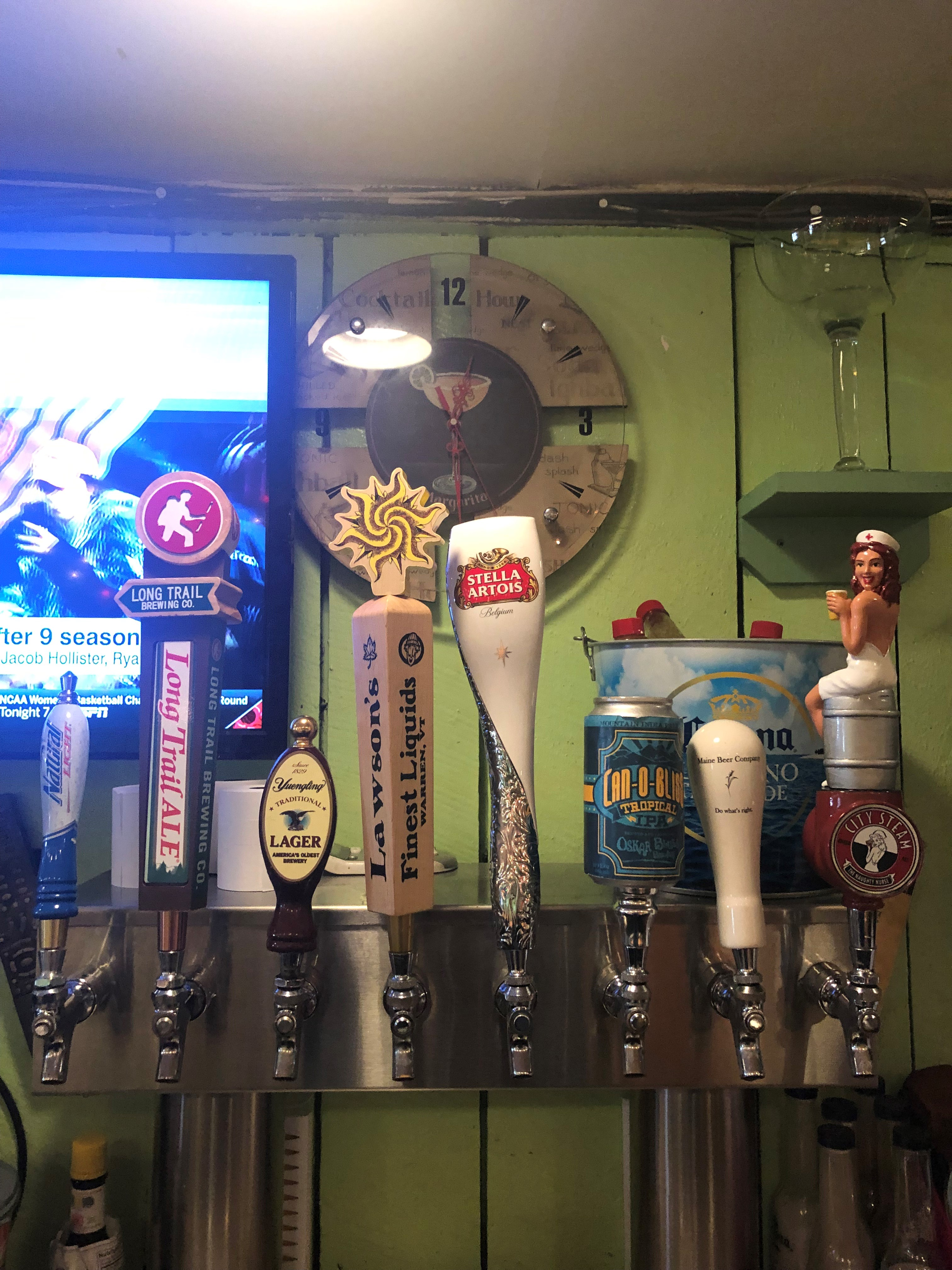 Beer taps against wall with clock and T V set.