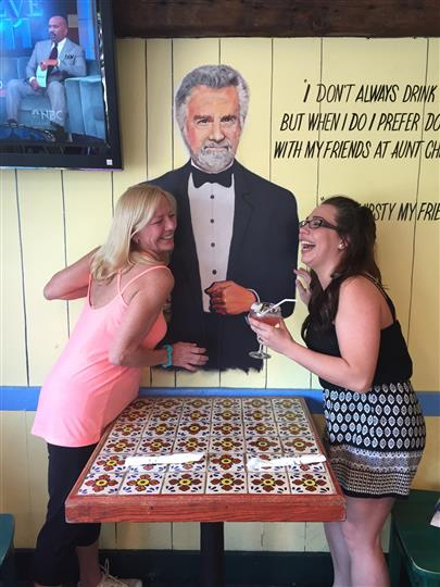 Two customers laughing with a painting of the most interesting man in the world