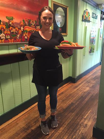 a waitress smiling and holding two plates of food