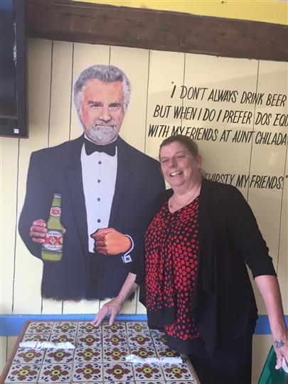 a customer smiling and posing next to the painting of the most interesting man in the world