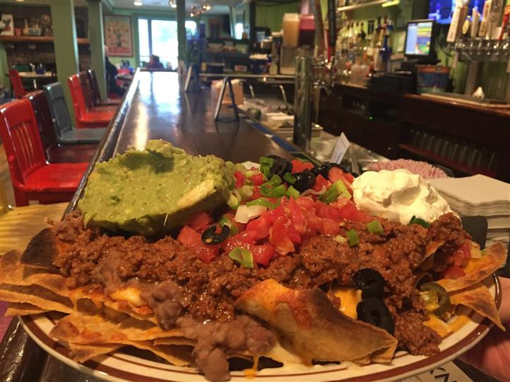a plate of nachos with beef, pico de gallo, guacamole, sour cream, olives, and cheese on top