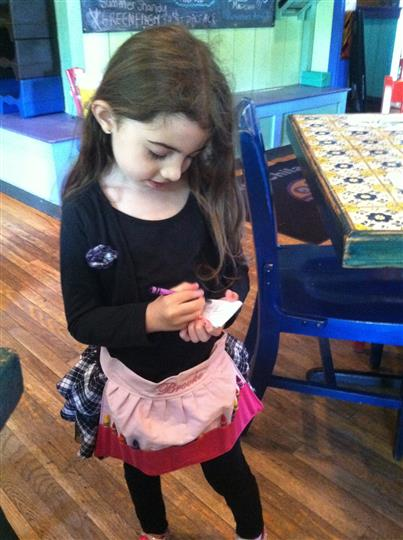 a little girl pretending to take orders with a crayon