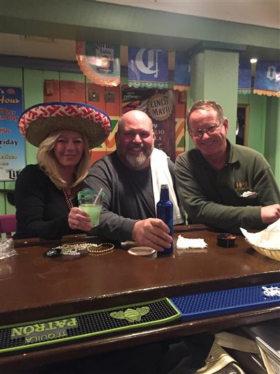 three customers happily smiling with their drinks and one customer wearing a sombrero