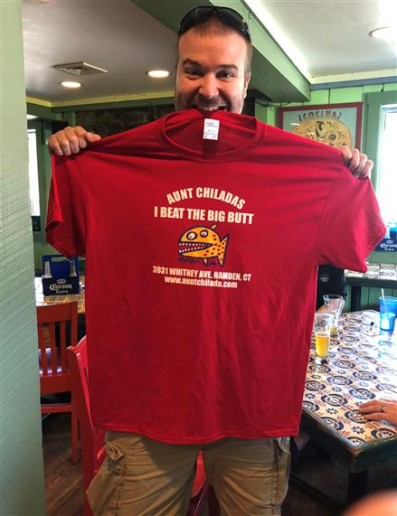 Man holding red tee shirt in hands and teeth.  Tee shirt reads Aunt chiladas. I beat the big butt.  3931 whitney avenue, hamden connecticut. www.auntchilada.com