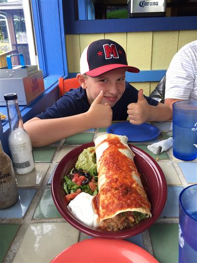 a customer putting his thumbs up next to a giant enchilada