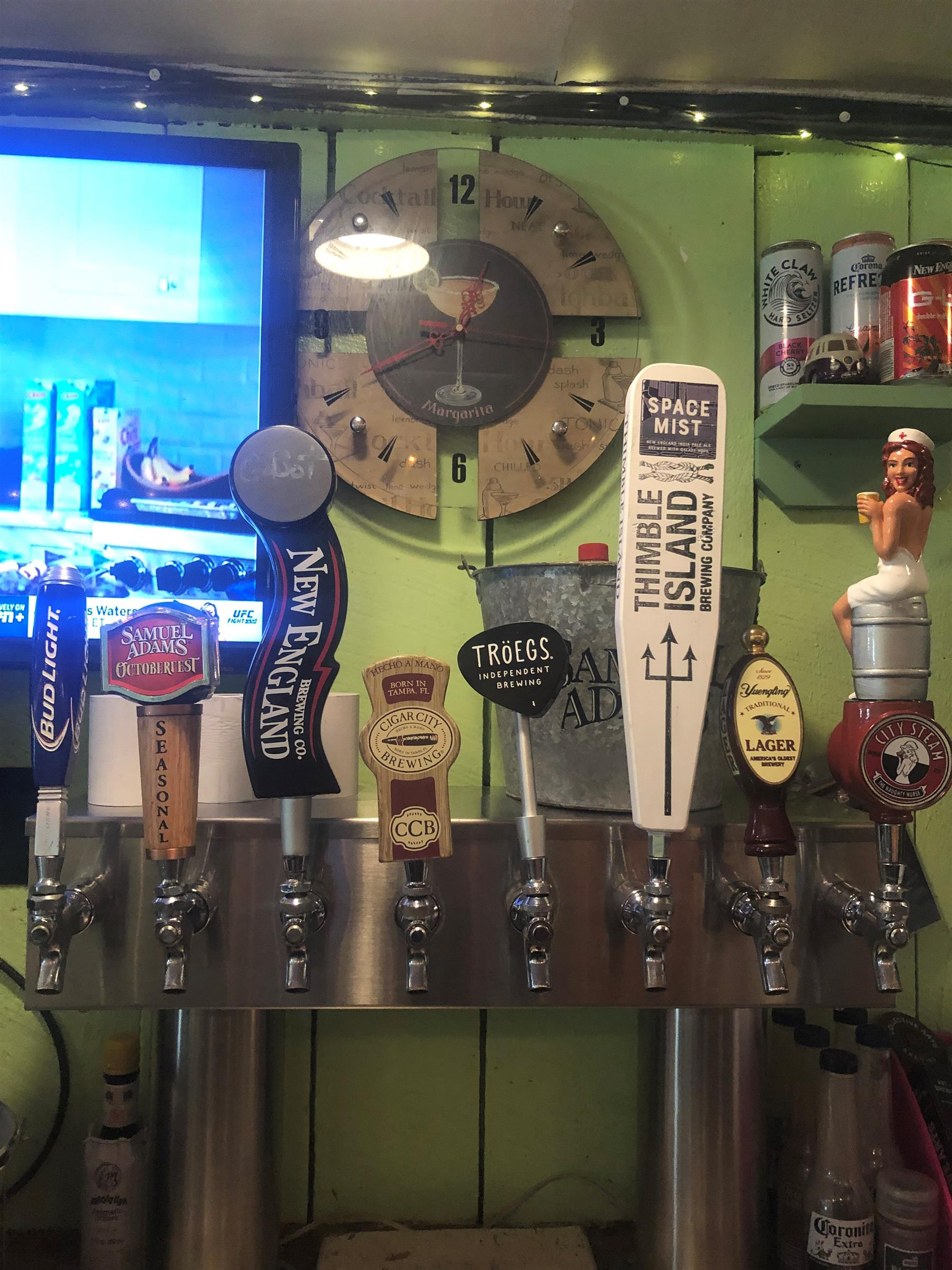 Beer taps in front of wall and television set