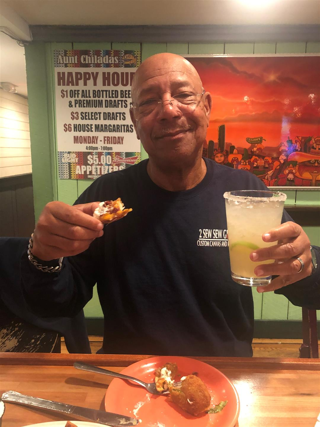 happy customer with a margarita and appetizer in his hand