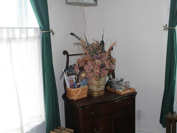 Dresser with a flower bouquet and a basket of books and assorted toiletries