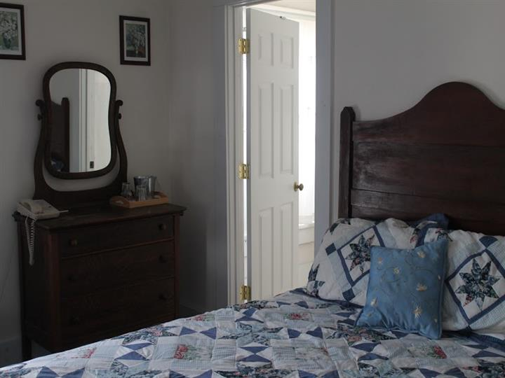 Bedroom with a side desk and mirror, doorway and a picture on a wall