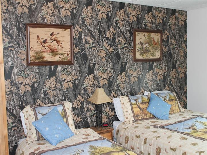 Bedroom with two twin beds, textured wallpaper and picture frames on the wall