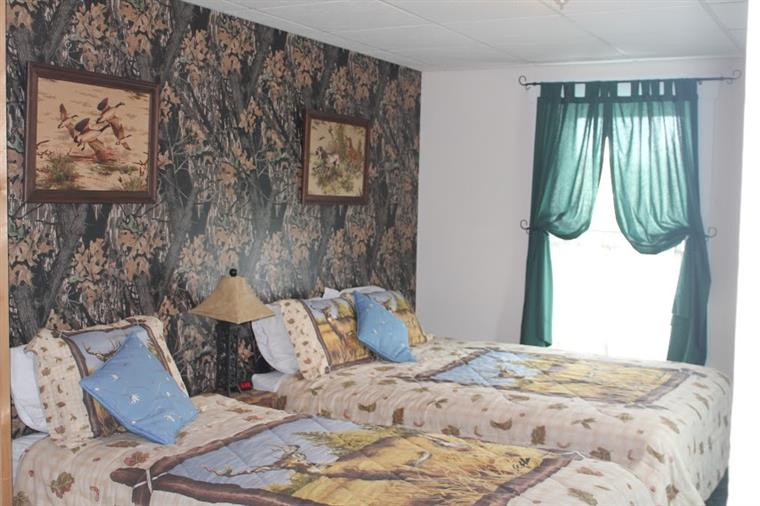 Bedroom with two twin beds, textured wallpaper amd picture frames on the wall