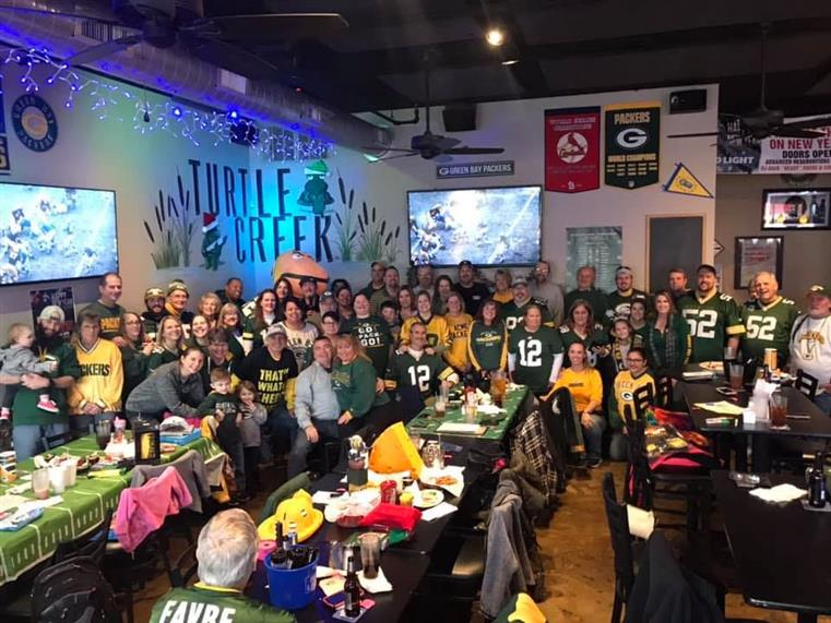 filled dining room crowd with Packers football jerseys for game night