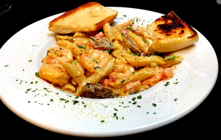 penne pasta with a pink cream tomato sauce served with shrimp, mushrooms and garlic bread