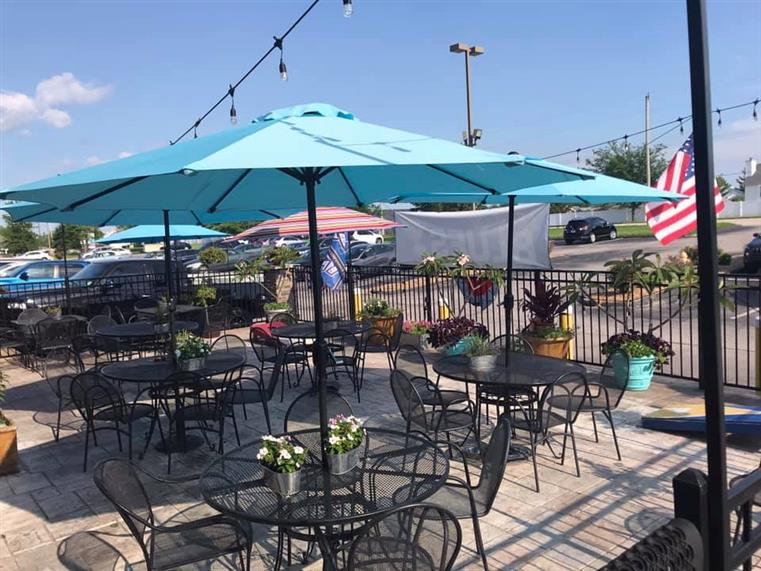 outdoor seating area with umbrellas, string lights and potted plants