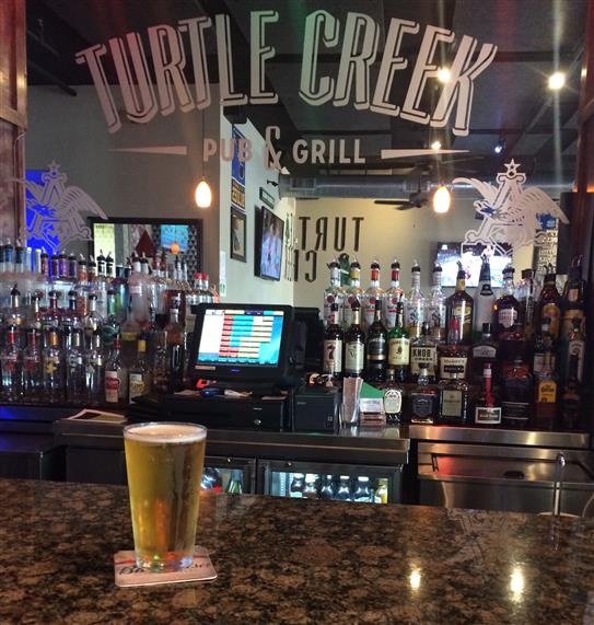 pint of beer on the bar with turtle creek pub and grill sign on bar mirror wall
