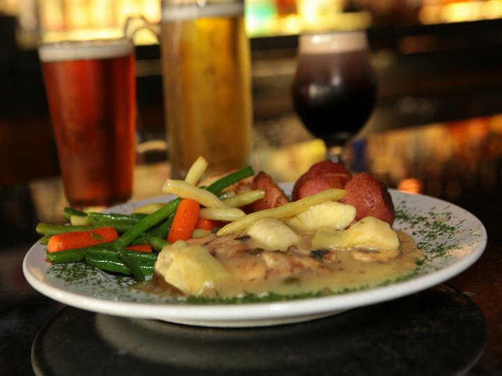 Chicken piccata with red potatoes, carrots and string beans in front of three full beer glasses