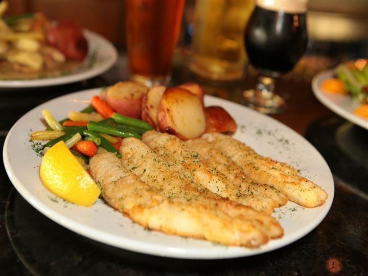 Lake perch golden fried with red potatoes, carrots, string beans in front of three full beer glasses.
