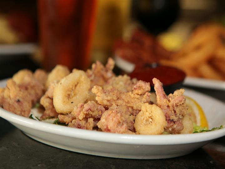 Plate of fried calamari with marinara and lemon wedge in front of beer glasses