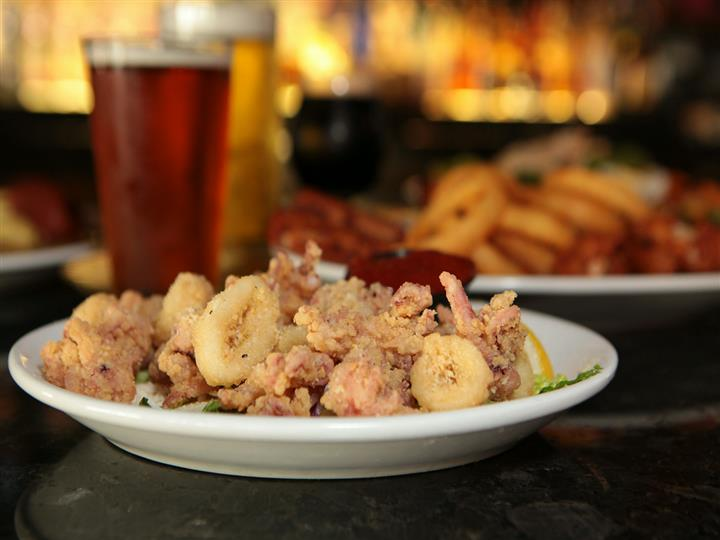 Plate of fried calamari with marinara and lemon wedge in front of beer glasses and plate of wings and onion rings