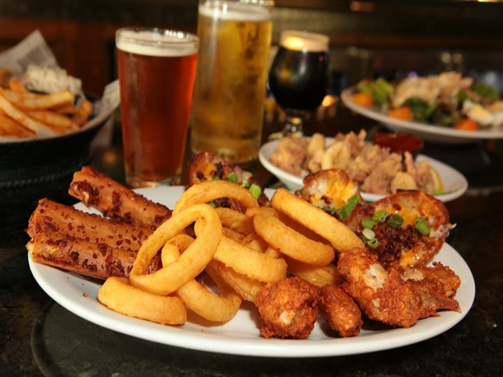 Plate of onion rings, breaded shrimp, baked potatoes in front of assorted appetizer plates and three full beer glasses.
