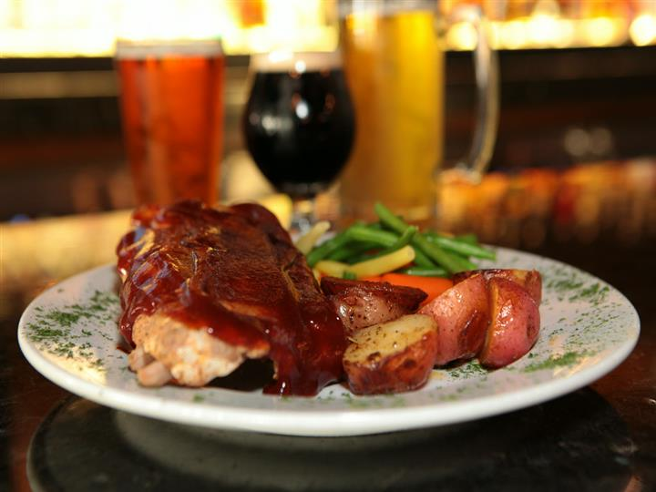 Ribs with Barbecue sauce, red potatoes, string beans and carrots. Beer and wine glasses in background.
