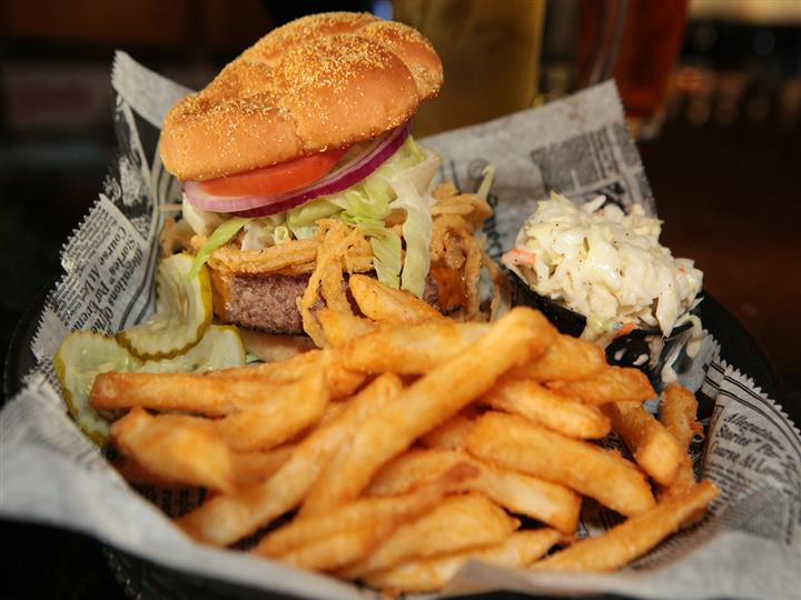 Hamburger with onion straws, lettuce, tomato, onions and pickles and coleslaw on the side.  Side of french fries all in basket.