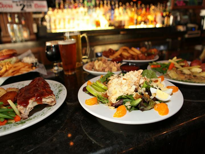 Variety of plates on bar counter - salad, ribs and potatoes, chicken piccata, onion rings with three full beer glasses