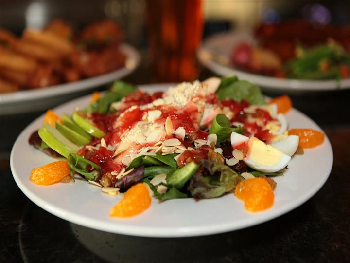 Salad with lettuce, orange slices, eggs, almonds with beer glass and appetizer plates in background