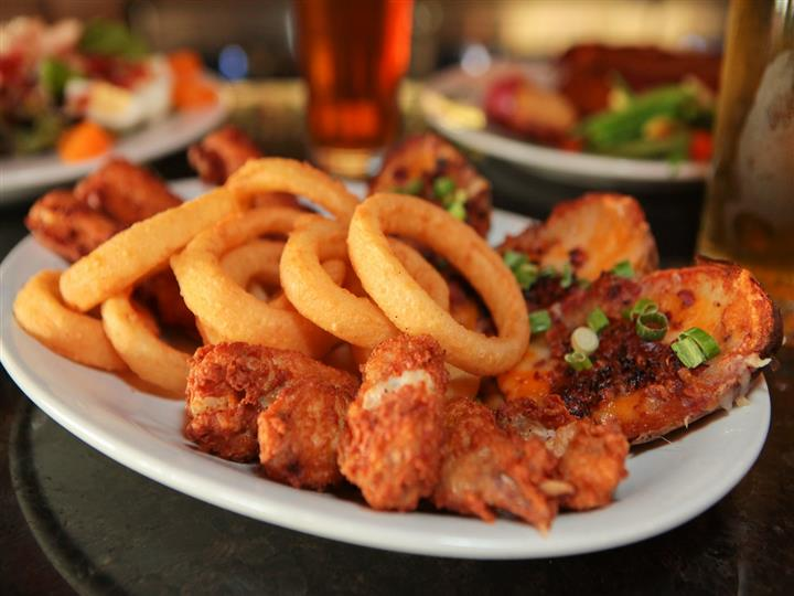 Plate of chicken wings, onion rings, baked potatoes with full beer glasses and more plates of appetizers.