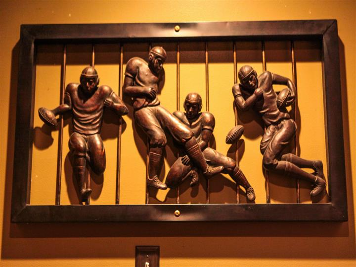 Artwork on wall of sculpted miniature football players.