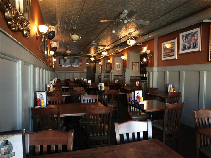Dining section with wood tables and chairs between two walls decorated with televisions and framed pictures.