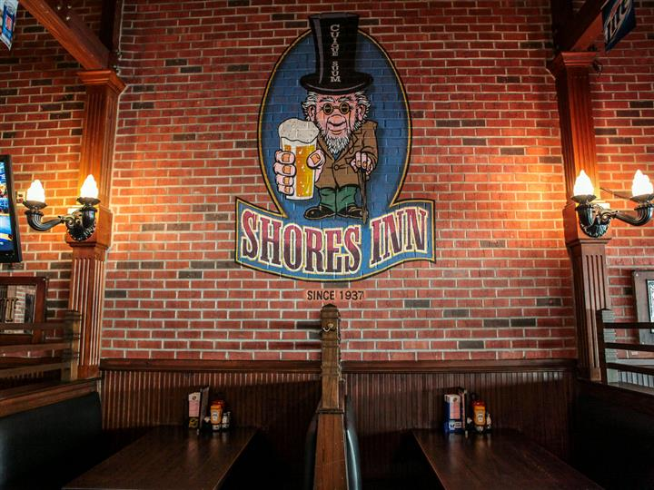 Shores Inn since 1937 logo painted on brick wall above wooden dining booths.