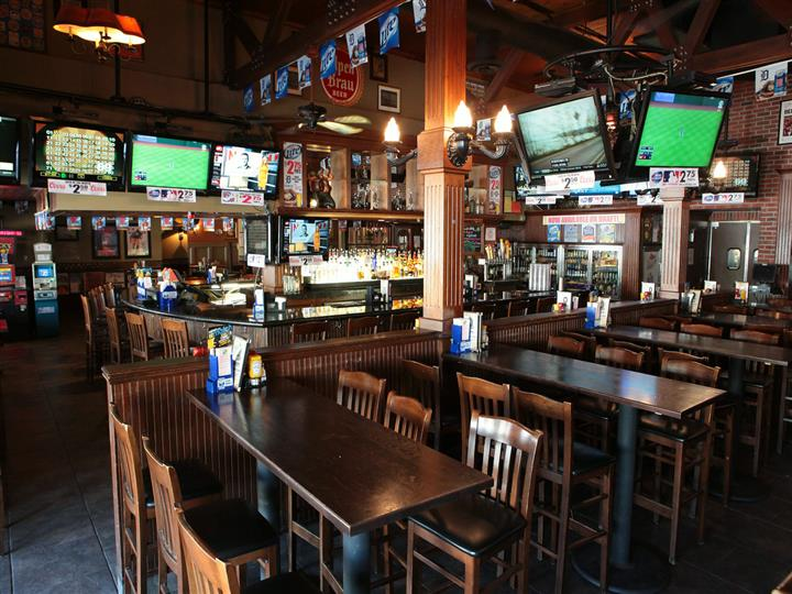 Dining and bar area with wooden tables, chairs, columns and dividers. Television sets on walls and pennants hang over bar.