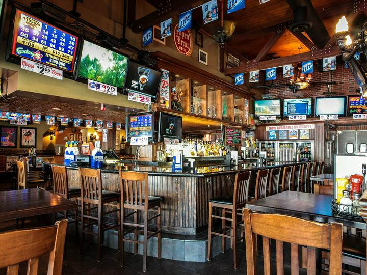 Dining and bar area. Wood chairs, tables, bar. Multiple TVs on walls.