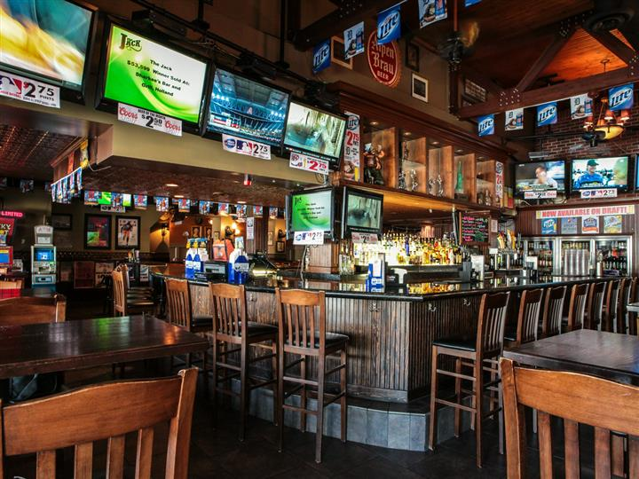 Bar and dining area. Wood bar and chairs, wood dining tables and chairs. Liquor bottles showing behind bar. Beer pennants hanging over bar. Multiple television sets on walls.