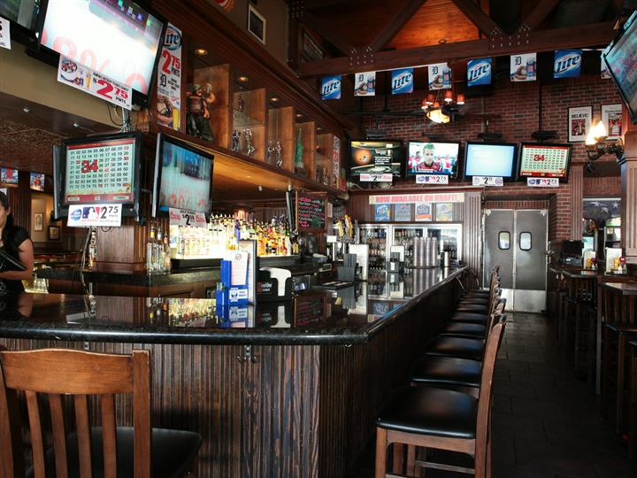 Bar area with wooden bartop, wood chairs, liquor bottles behind bar and figurines on shelf. Pennants hang above bar.