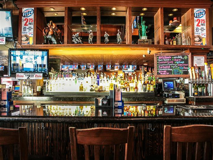 Bar area with wooden bartop, wood chairs, liquor bottles behind bar and figurines on shelf.