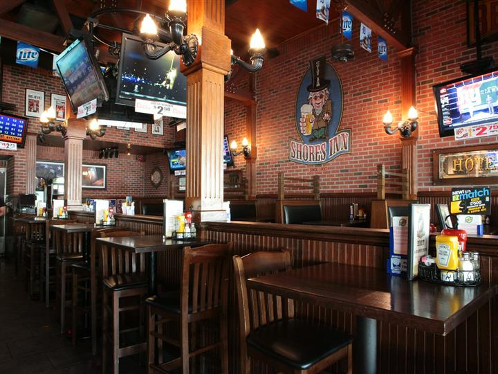 Wooden dining tables, chairs, and booths. Walls are brick texture and have multiple TV screens