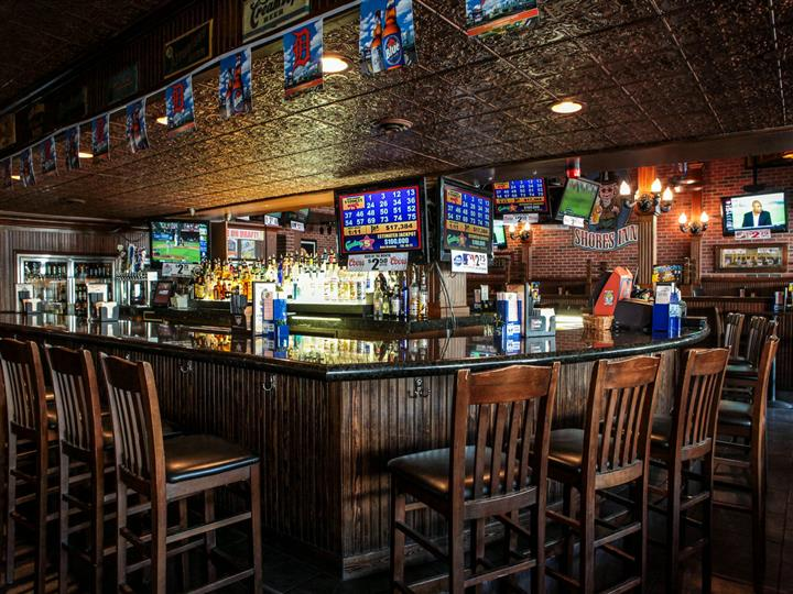 Bar area. Wood bar and chairs. Liquor bottles showing behind bar. Beer pennants hanging over bar.