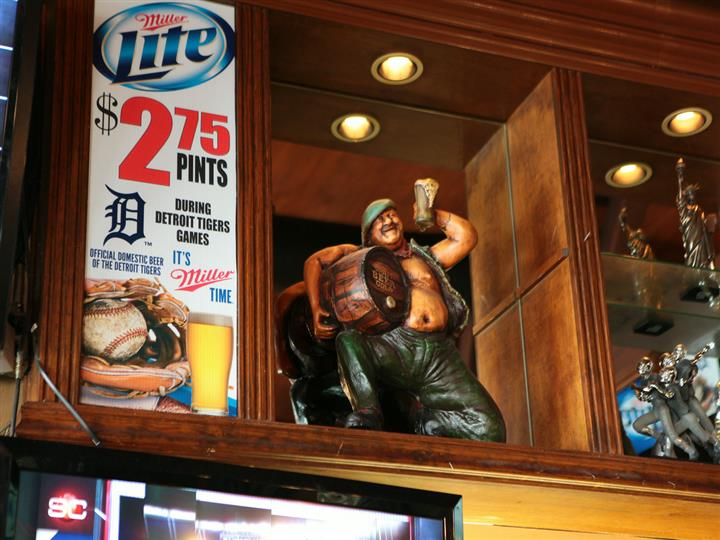 Miller lite sign on wall. $2.75 pints during detroit tigers games. Official domestic beer of the detroit tigers. It's miller time. Adjacent is wood figurine of man holding beer barrel.