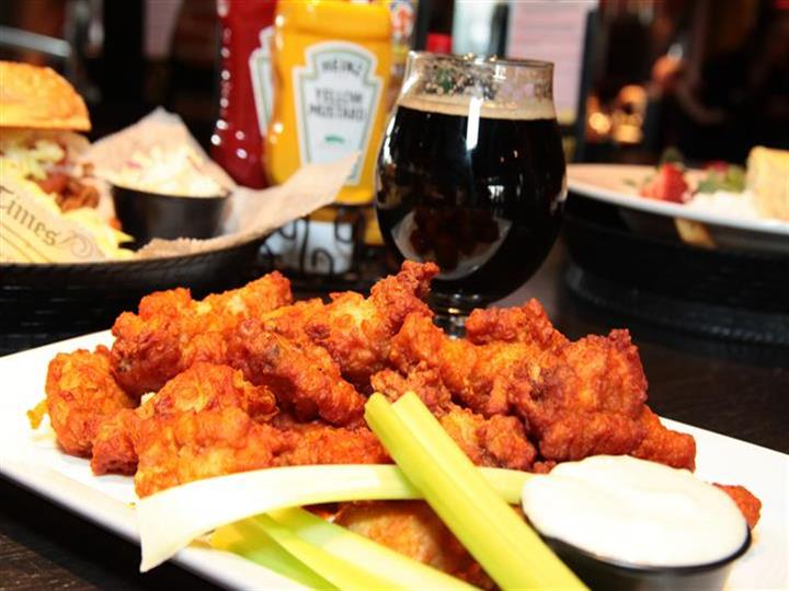 Boneless chicken wings with celery and bleu cheese dressing in front of beer and other entrees.