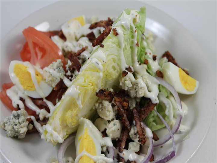 Salad with boiled eggs and bacon drizzled in ranch sauce