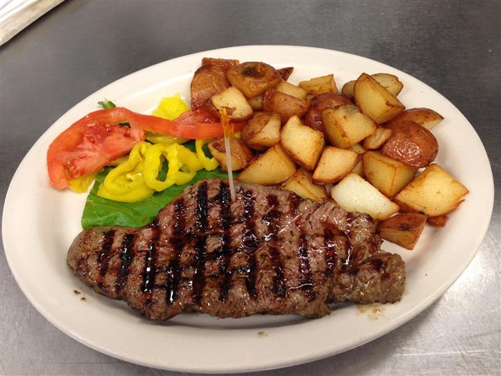 Steak and potatoes with vegetables to the side