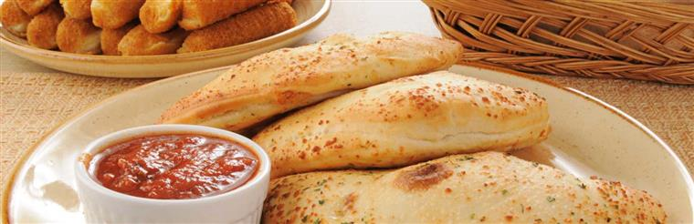 Three calzones with marinara sauce on white dish.
