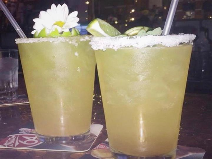 two margaritas with salt rim and lime wedges