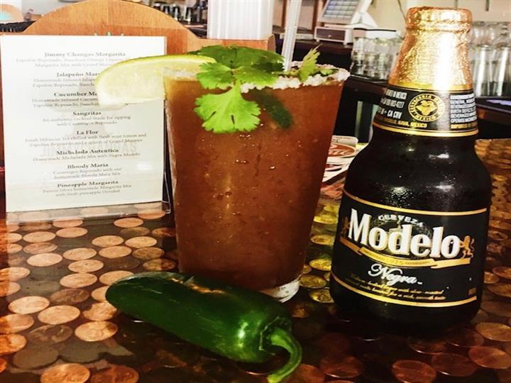 a glass of bloody mary with a jalapeno pepper, lime wedge, and a bottle of modelo beer next to it