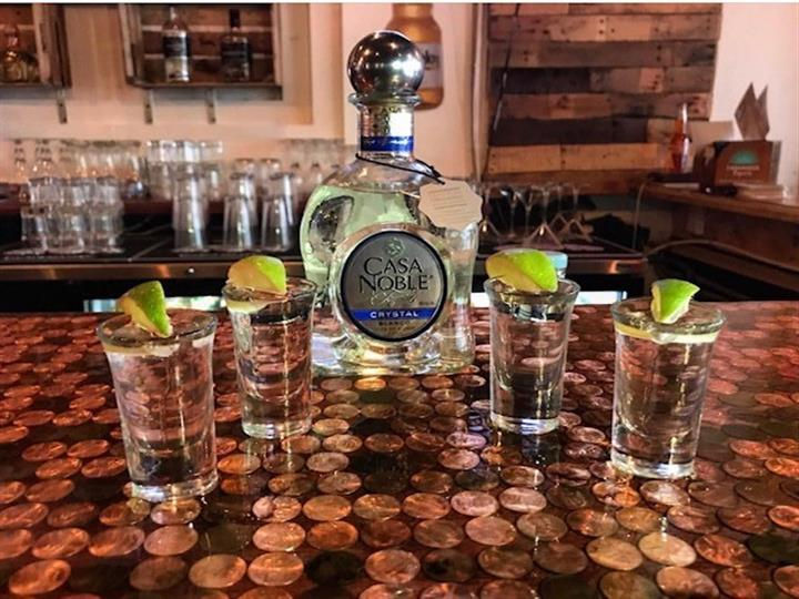 casa noble tequila with four shots around it with lime wedges