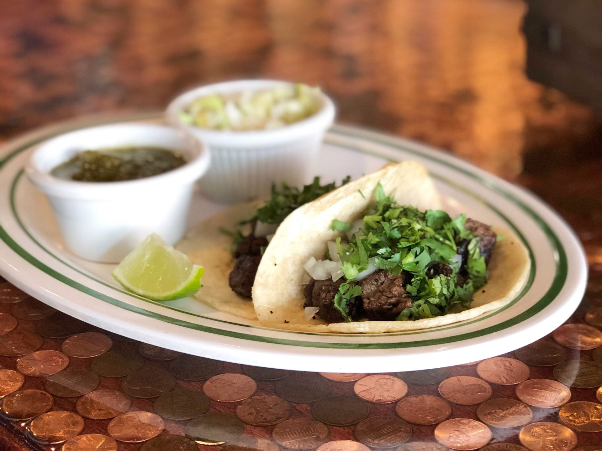 Steak street tacos on a plate with a lime wedge