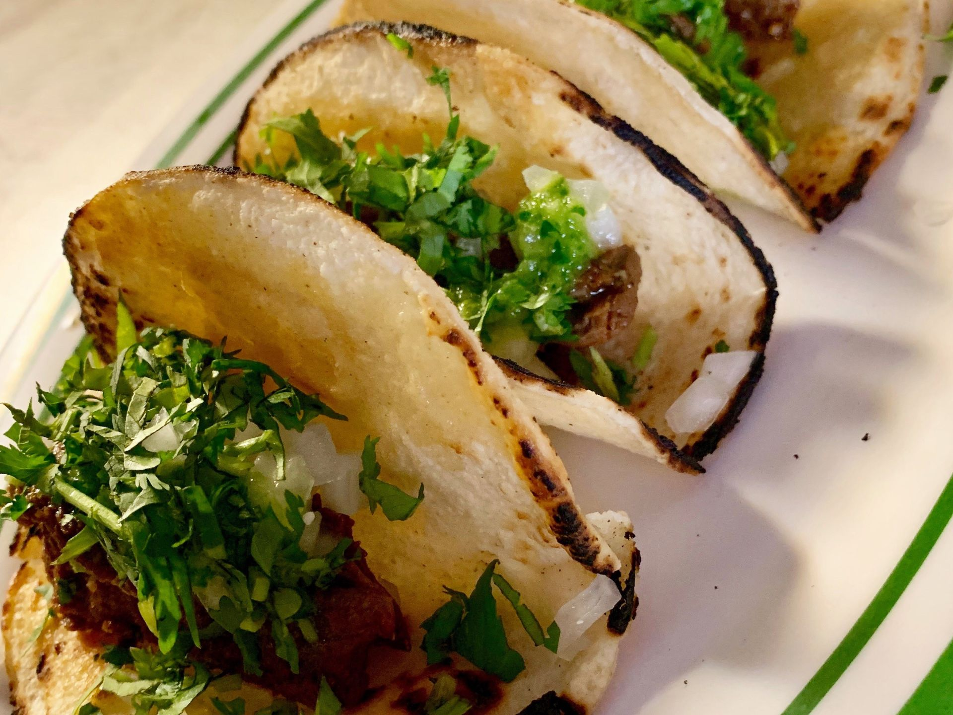 Steak street style tacos in corn tortilla shells on a plate